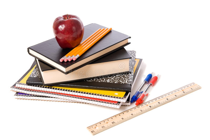 Apple and school Supplies on a white background. A group of assorted school supplies on a white background with books, pencils, a ruler, notebooks, and ann apple royalty free stock images