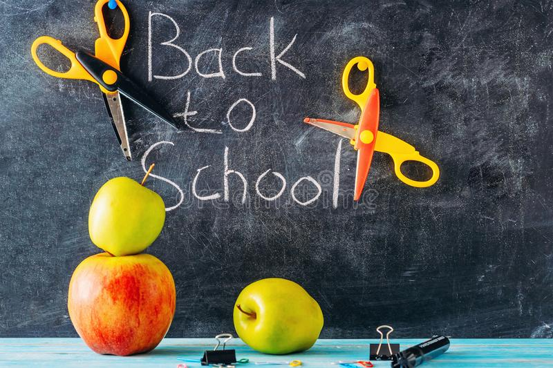 Apple, scissors and school supplies against blackboard with `back to school` on background. Still life with apple, scissors and school supplies against stock photo