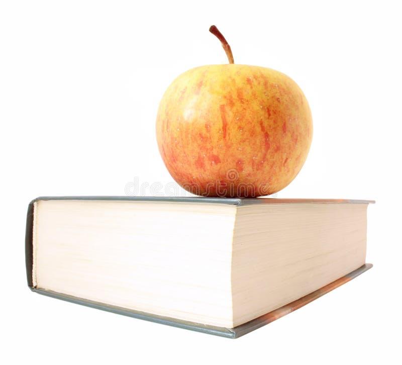 Apple si trova sull'angolo del libro chiuso fotografia stock