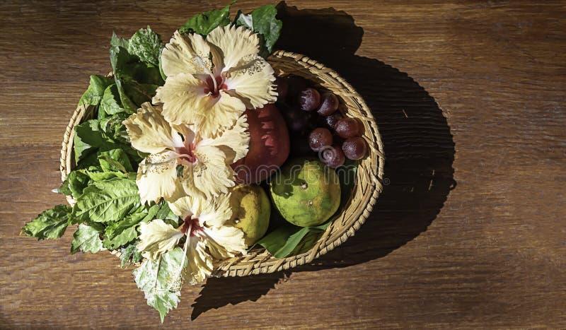 Apple, Sinaasappel en druif in de manden van het weefselbamboe met bloemendecoratie op houten lijst stock afbeelding