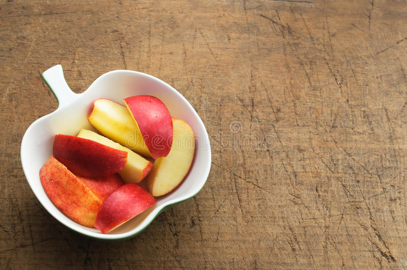 Apple Slices in Apple Form Bowl. On old cutting board stock image
