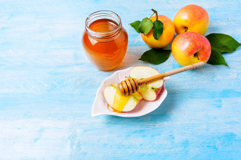 Apple slices with honey on blue wooden background royalty free stock photos