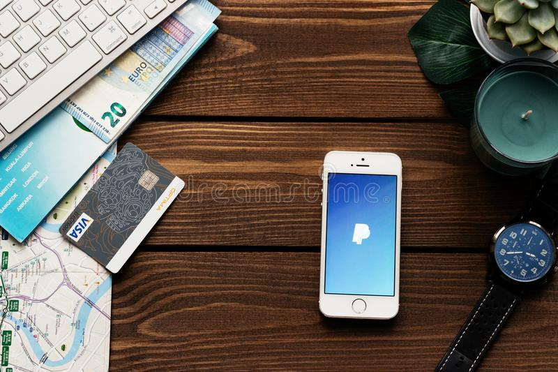 Apple smartphone with PayPay payment app. Flat lay with wooden table background. Succulent plant, watch, keyboard. Credit bank car. MINSK, BELARUS - March 3,2018 stock image