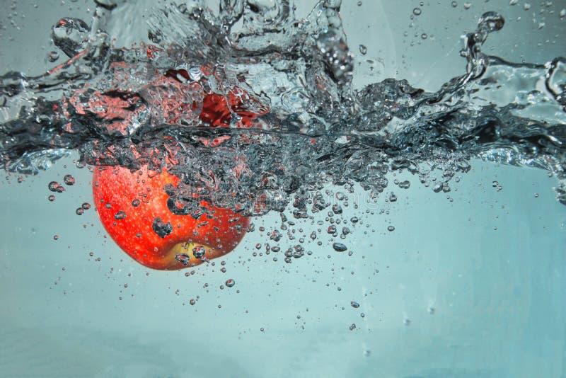 Apple som plaskar in i vattnet royaltyfri foto