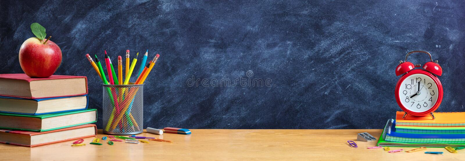 Apple On Stack Books With Pencils And Alarm Clock stock image