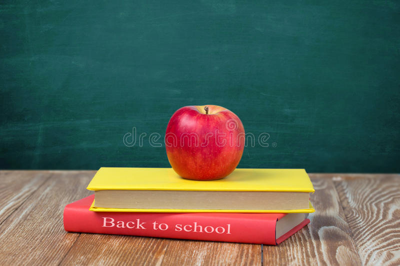 Download Apple On Stack Books Wooden Table Blackboard Background Stock Photo