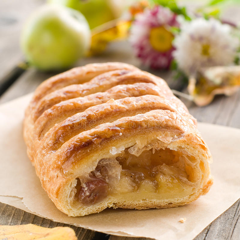Apple strudel. Slice of an apple strudel on a baking paper royalty free stock image