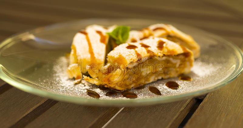 Apple strudel. Slices on a glass plate on wooden table stock photography
