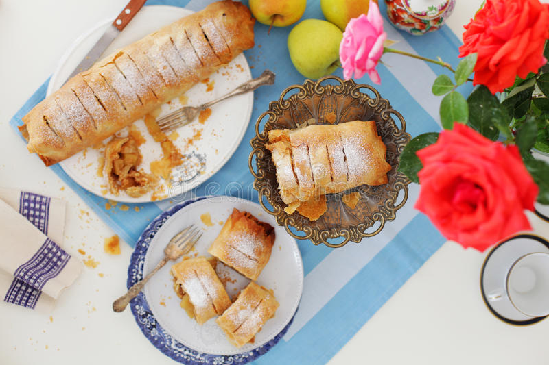 Apple Strudel or Apfelstrudel. Apfelstrudel, apple strudel , german apple pie or stroodel is a typical dessert in Bavaria and Austria. Conceptual tablesetting royalty free stock image