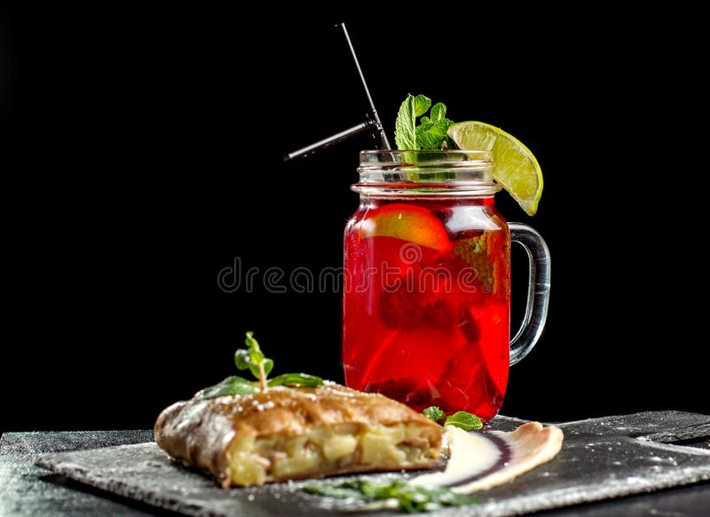 Apple strudel, garnished with mint and sprinkled with powdered sugar. Sstrudel, in the background is a hot drink with mint and lime. Side view royalty free stock images