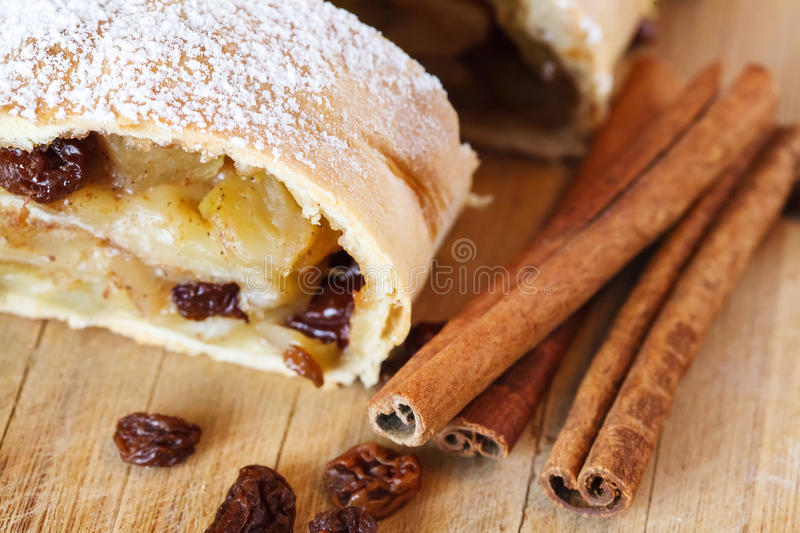 Apple strudel with icing sugar, cinnamon sticks, wooden background stock images