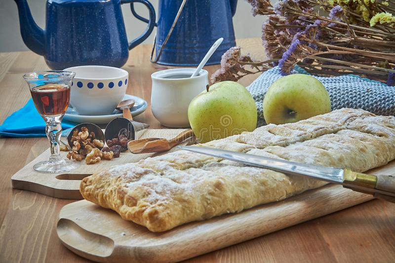 Apple strudel with nuts, raisins, cinnamon and powdered sugar. Homemade apple strudel with fresh apples. Country style apple stock images