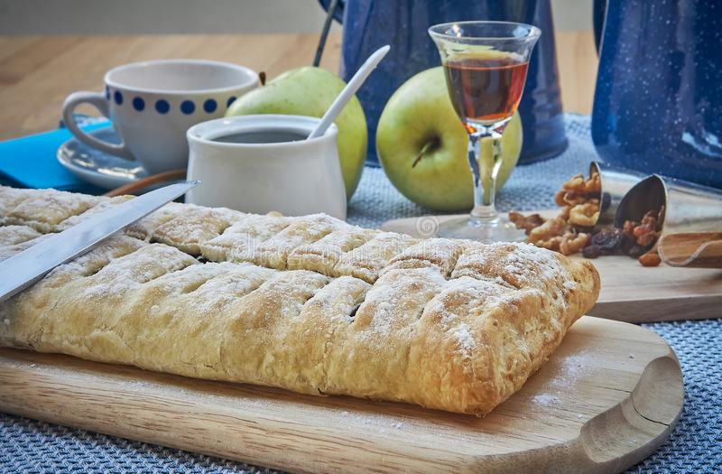 Apple strudel with nuts, raisins, cinnamon and powdered sugar. Homemade apple strudel with fresh apples. Country style apple stock photography