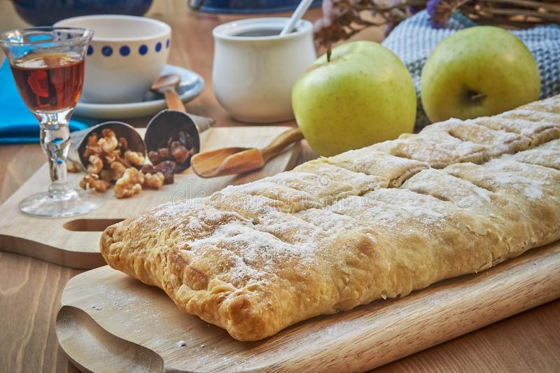 Apple strudel with nuts, raisins, cinnamon and powdered sugar. Homemade apple strudel with fresh apples. Country style apple royalty free stock image