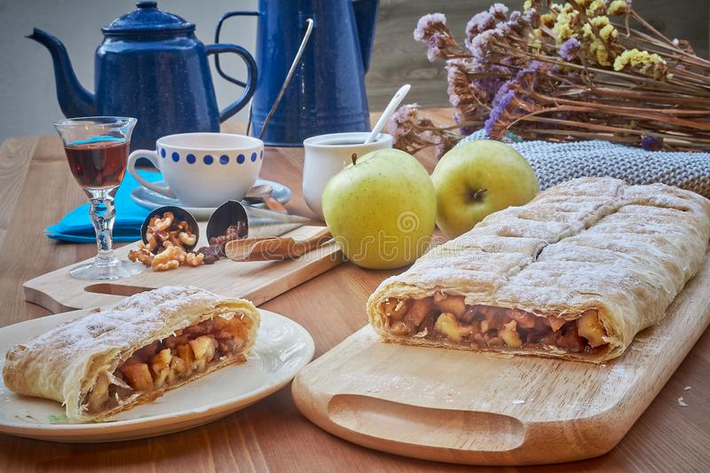 Apple strudel with nuts, raisins, cinnamon and powdered sugar. Homemade apple strudel with fresh apples. Country style apple. Strudel stock photo