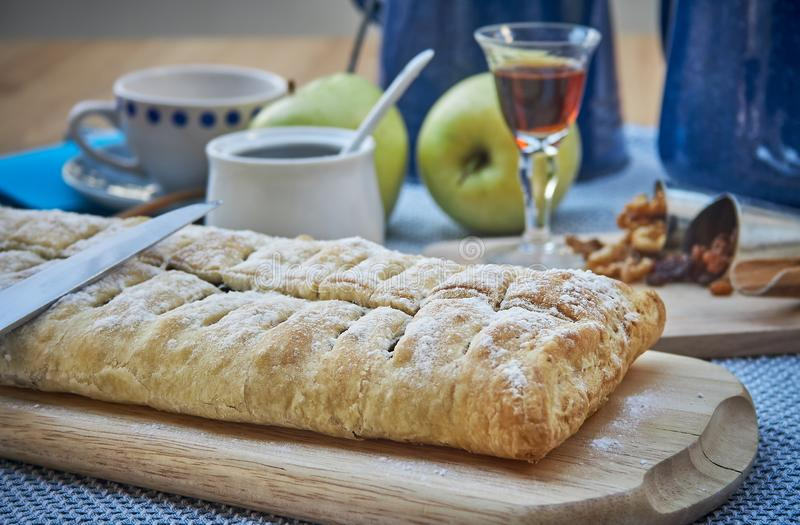 Apple strudel with nuts, raisins, cinnamon and powdered sugar. Homemade apple strudel with fresh apples. Country style apple stock photo