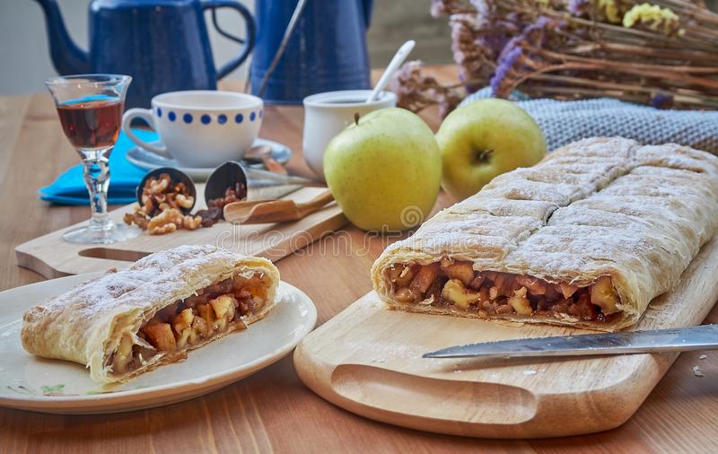 Apple strudel with nuts, raisins, cinnamon and powdered sugar. Homemade apple strudel with fresh apples. Country style apple royalty free stock photography