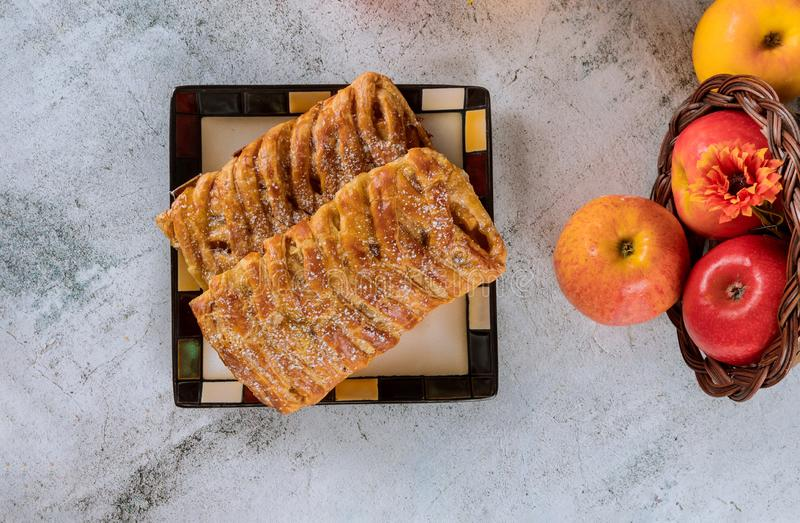 Apple strudel on square plate with apples. On white table, dessert, europe, autumn, sweet, puff, pastry, crispy, food, cake, pie, fruit, sugar, homemade, bakery royalty free stock images