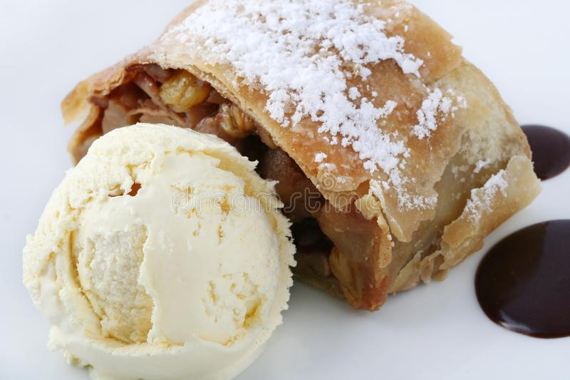 Apple strudel. With vanilla ice cream, garnished with chocolate and powdered sugar on a white plate on a white background. Close-up stock photos