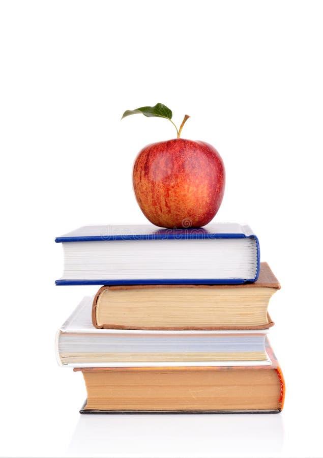 Apple su pochi libri di scuola su un fondo bianco fotografie stock