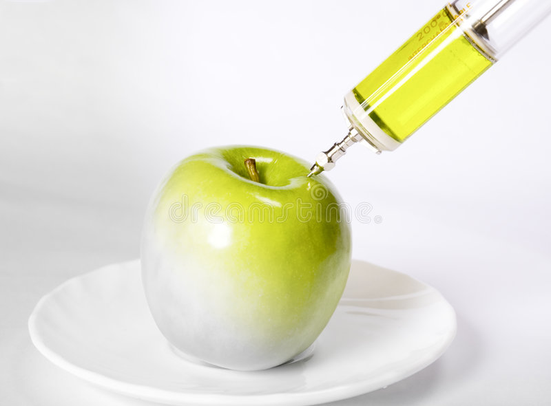 Apple with a syringe. Colouring an aplle with hypodermic syringe royalty free stock photos