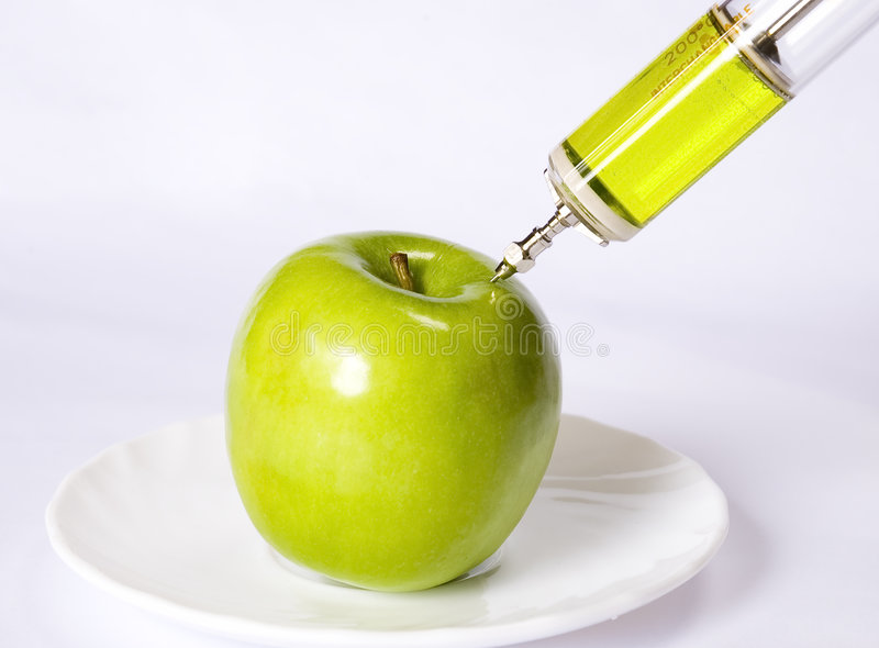 Apple with a syringe. A green apple being injected with a syringe containing green fluid stock photo