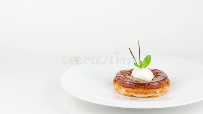 Apple tart Tatin. Individual upside down apple tart Tatin with Chantilly cream, mint and caramelised vanilla pod. A classic french dessert, isolated on white, my stock photography