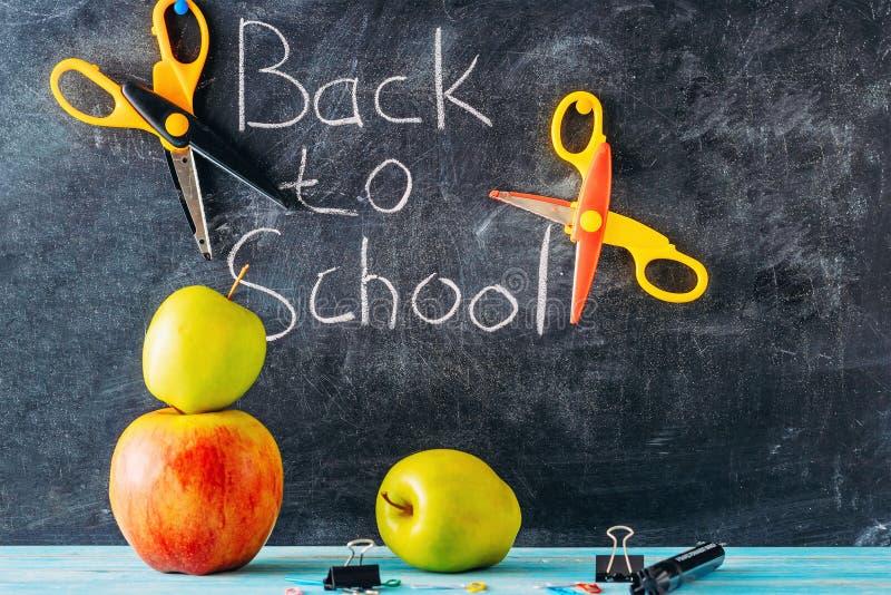 Apple, tesouras e fontes de escola contra o quadro-negro com ` de volta ao ` da escola no fundo foto de stock