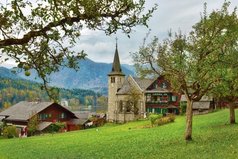 Apple trädgård framme av den gamla församlingkyrkan på en molnig höstdag Grundlsee Styria, Österrike fotografering för bildbyråer