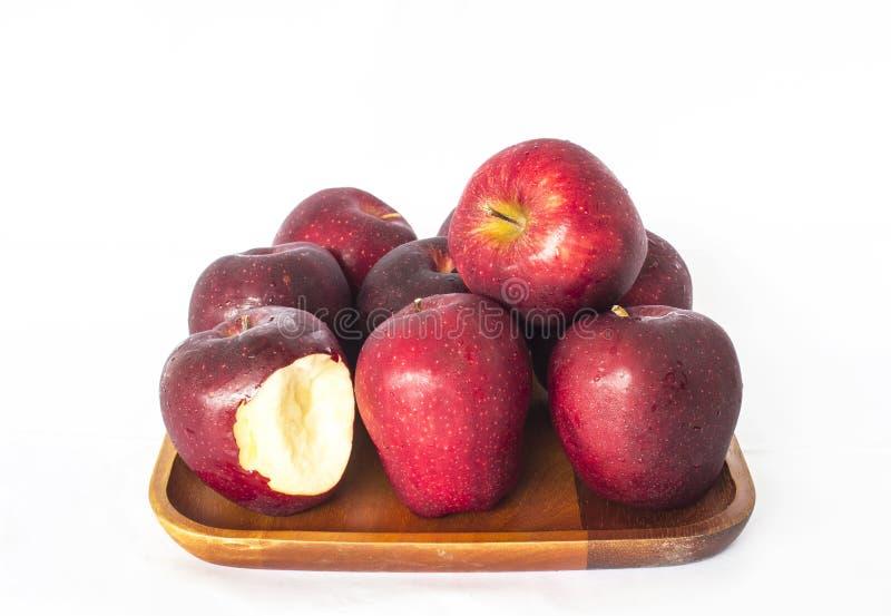 Apple a un endroit frais été perché sur un plat en bois avec une morsure mars photos libres de droits