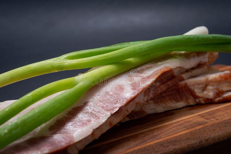 Apple Uncured fumou o bacon decorado com chalotas da cebola verde na placa de corte de madeira natural imagem de stock