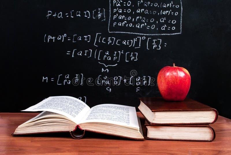 Apple und Bücher auf einem Holztisch und einer Schultafel mit mathematischen Gleichungen im Klassenzimmer stockfotografie
