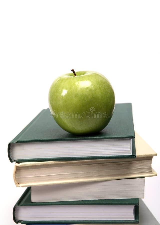 Apple und Bücher auf weißer Vertikale stockfotos
