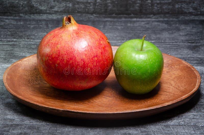 Apple und Granatapfel auf einer hölzernen Schüssel lizenzfreie stockfotos