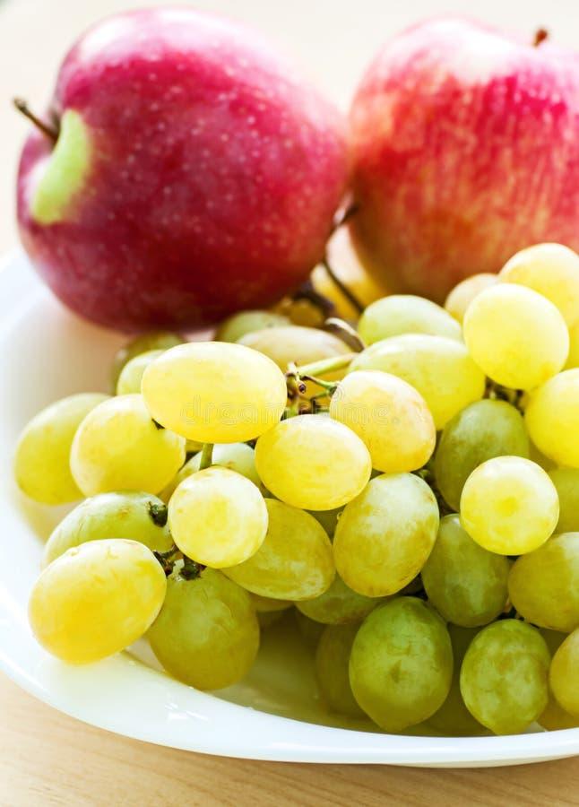 Apple und Traube tragen auf Teller Früchte stockfotos