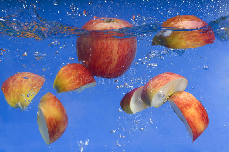Apple under water with a trail of transparent bubb. Les in blue stock image