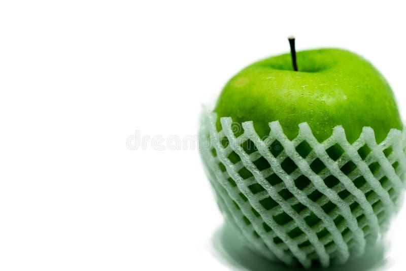 Apple verde aislado en el fondo blanco con descenso del agua en a toda profundidad del campo con la trayectoria de recortes imagen de archivo libre de regalías