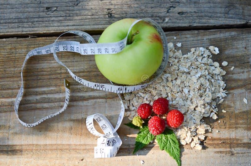 Apple verde avvolto con nastro adesivo di misurazione accanto al lampone con le foglie e un mazzo di farina d'avena fotografie stock libere da diritti