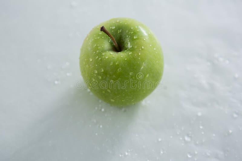 Apple verde con las gotitas de agua fotografía de archivo