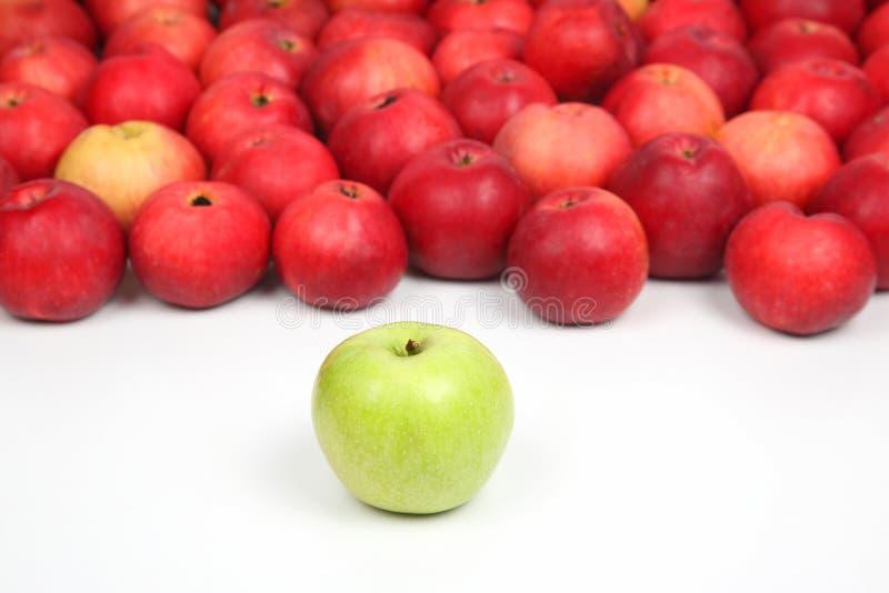 Apple verde em um fundo de maçãs vermelhas no fundo branco fotos de stock
