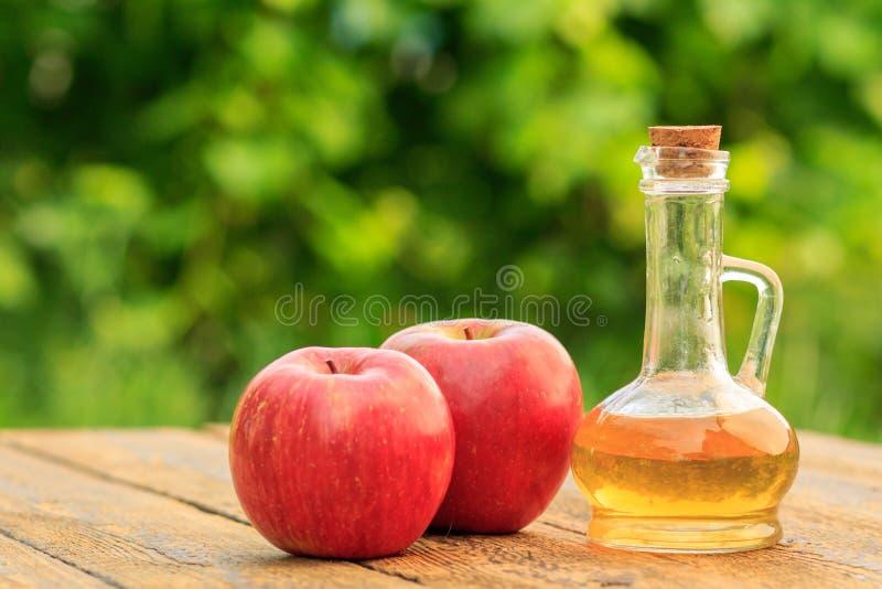 Apple vinäger i glasflaska och nya röda äpplen på träboa arkivfoton