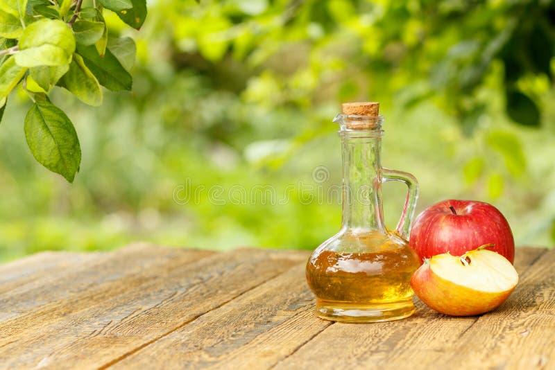 Apple vinäger i glasflaska och nya röda äpplen på träboa royaltyfri bild