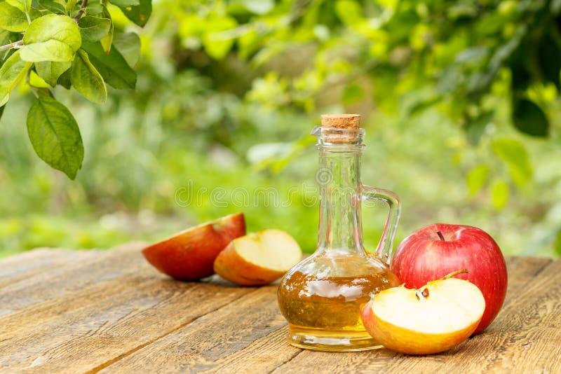 Apple vinäger i glasflaska och nya röda äpplen på träboa royaltyfria bilder