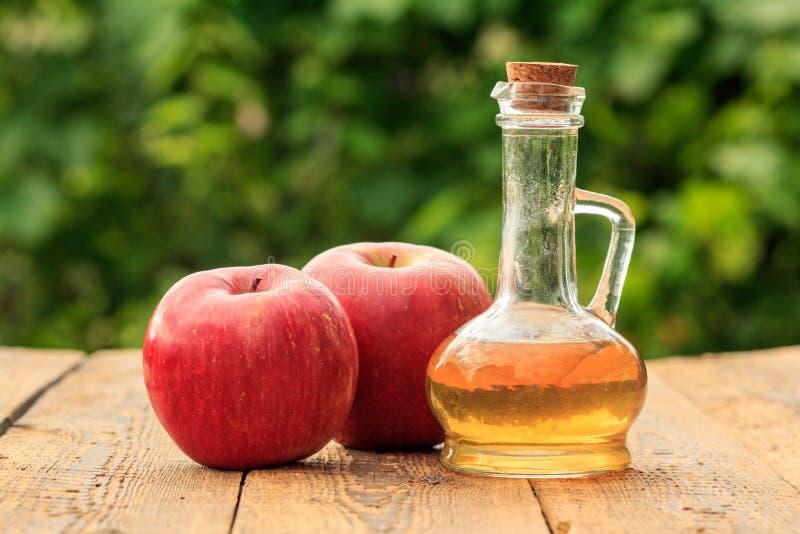 Apple vinäger i glasflaska och röda äpplen på träbräden med grön naturlig bakgrund royaltyfri bild