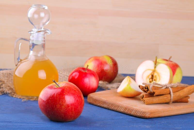 Apple vinäger med mogna äpplen på en blå träbakgrund royaltyfria foton