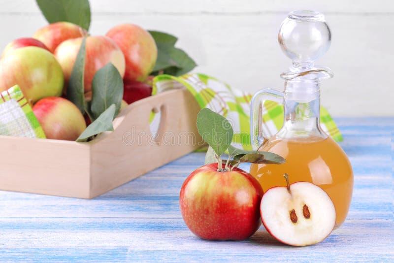 Apple vinäger med mogna äpplen på en blå träbakgrund arkivfoto