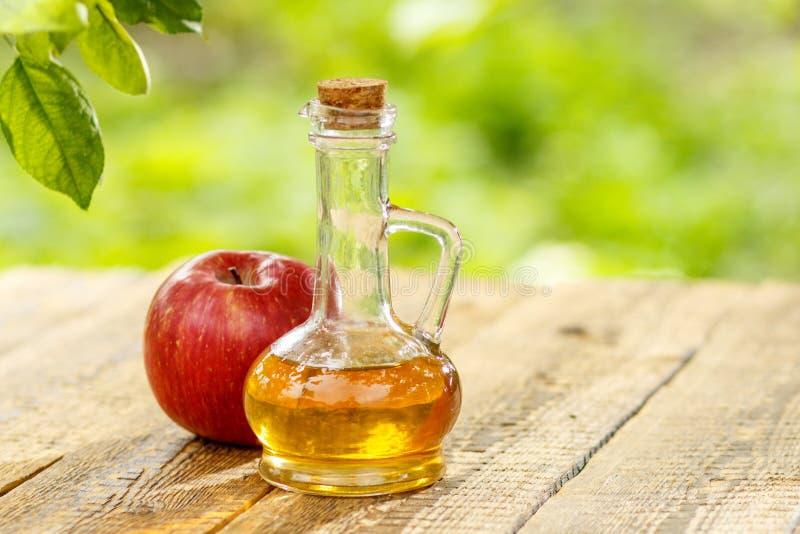 Apple vin?ger i glasflaska och nytt r?tt ?pple p? tr?galt arkivfoton