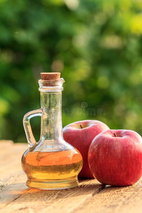 Apple vinegar in glass bottle and fresh red apple on wooden boards with green natural background. Apple vinegar in glass bottle with cork and fresh red apples on royalty free stock photos