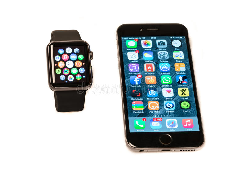 Apple Watch and iPhone. Ostfildern, Germany - May 13, 2015: The new Apple Watch, a black 42mm Apple Watch Sport displaying the apps screen next to the iPhone 6 stock photo