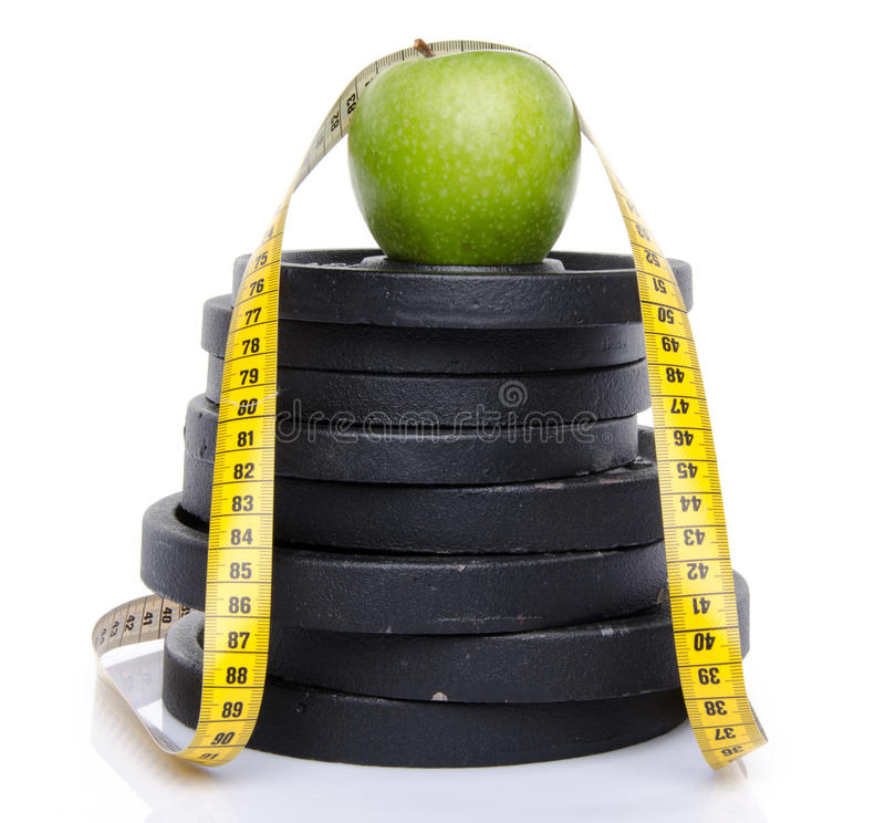 Apple on weights with a tape measure. Isolated on white stock images